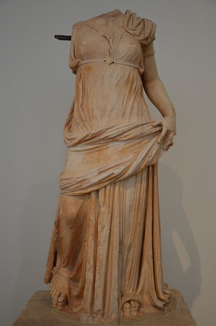 Statue of a woman wearing a transparent chiton, girt high, a himation and elaborate sandals, she wears an armlet on the left arm and bracelet on the wrist found in Piraeus, 1st century BC, National Archaeological Museum of Athens