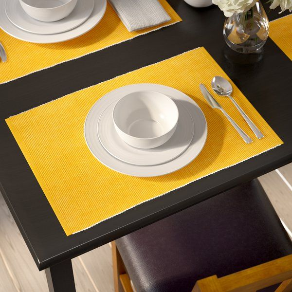 Instantly elevate any dinner party or family meal with this four-piece set of ribbed placemats. Made from 100% cotton, each machine washable placemat strikes a classic rectangular shape with stitch-reinforced hems in a solid-hue with a subtle white fringe to match with any aesthetic. Establish an inviting, transitional tablescape in your dining room by rolling out a bright medallion area rug for a pleasant pop of pattern, then arrange linen-upholstered parsons chairs around a clean-lined…