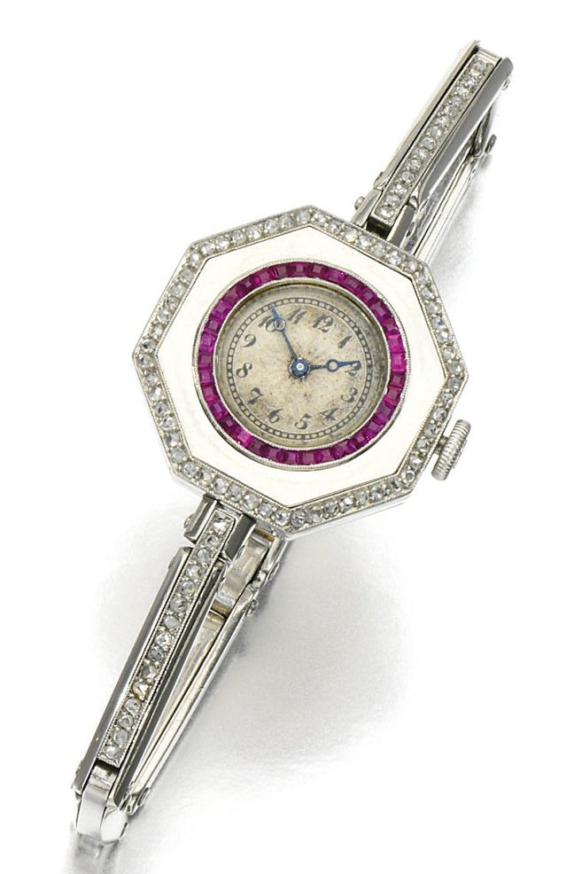 LADY'S RUBY AND DIAMOND COCKTAIL WATCH, 1920S.   The circular dial applied with Arabic numerals framed within a calibré-cut ruby border, inset to a hexagonal case decorated with rose diamonds, to an e