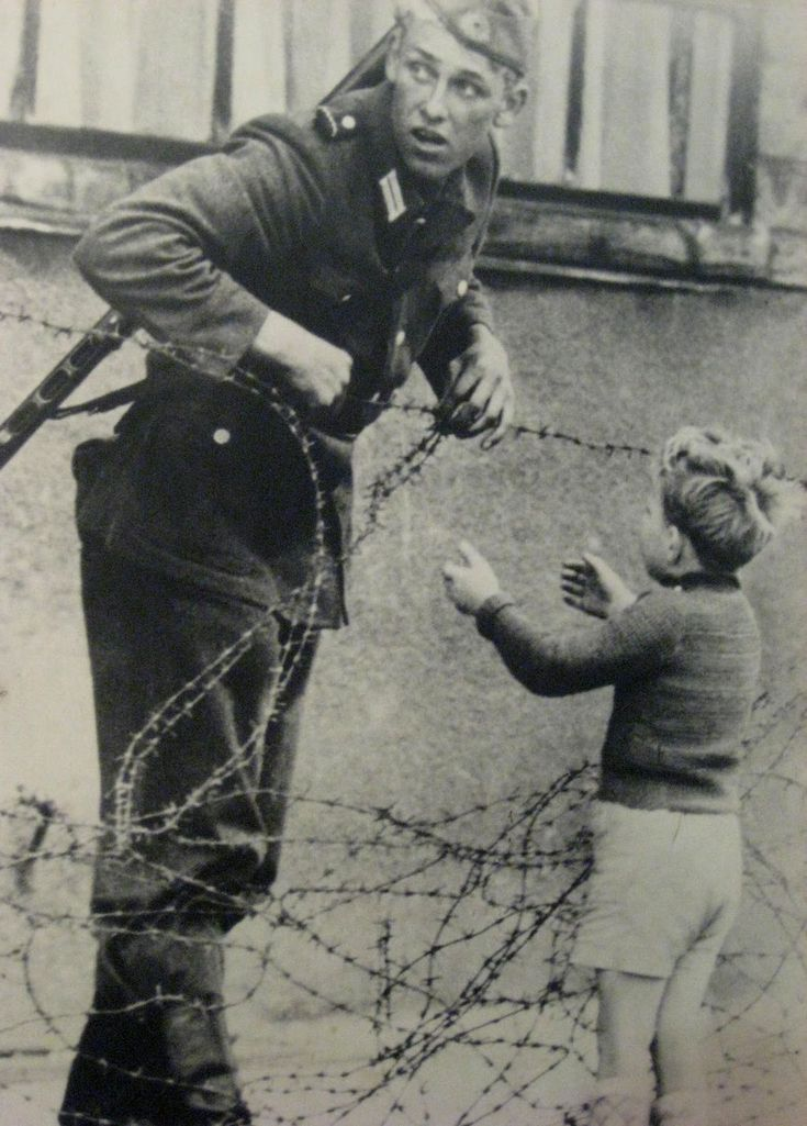 "Berlin, August 1961, the anniversary of the building of the Berlin Wall. With obvious apprehension, a young East German soldier glances about as he prepares to let a small boy pass through the emerging barrier. No doubt the boy spent the night with friends and found himself the next morning on the opposite side of the Wall from his family.  The soldier was seen by a superior officer who immediately detached him from his unit. ""No one,"" reads the inscription, ""knows what became of him."""