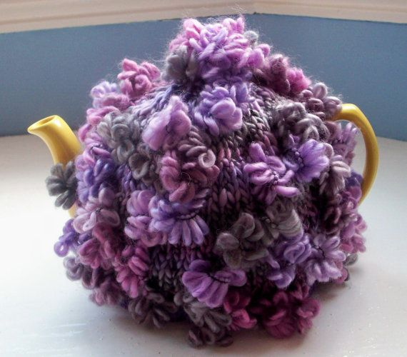 Tea cosy,lilac, rose, grey, pink, purple with flowers and flower pompom This one is a functional cozy to keep your teapot (and therefore your tea) warm longer - great for taking outside. I handknitted it from a wonderful novelty yarn - acrylic, with a touch of wool. It is in several tasteful shades of pink, purple and grey. This yarn is great fun - it produces random scattered flowers above the thick, cosy fabric. The lower edge has a band of purple wool ribbing and the cozy is finished…
