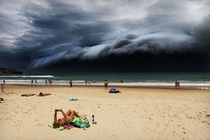 Nature, 1st prize singles Rohan Kelly, Australia, 2015, Daily Telegraph, Storm Front on Bondi Beach A massive 'cloud tsunami' looms over Sydney as a sunbather reads, oblivious to the approaching cloud on Bondi Beach, Sydney, Australia on 06 November 2015.