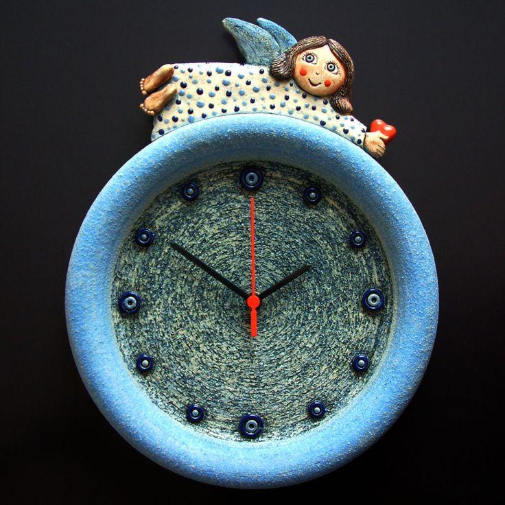 Hodiny s andílkem Keramické závěsné hodiny Modelováno z hrubé šamotové hlíny, glazováno matnými a lesklými glazurami. Rozměr 36 x 28,5 cm