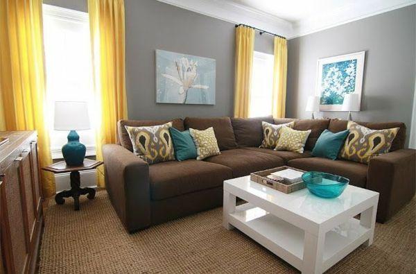 Graue Wandgestaltung mit Braunem Sofa und Gelb Blauen Kissen mit Weißem Tisch