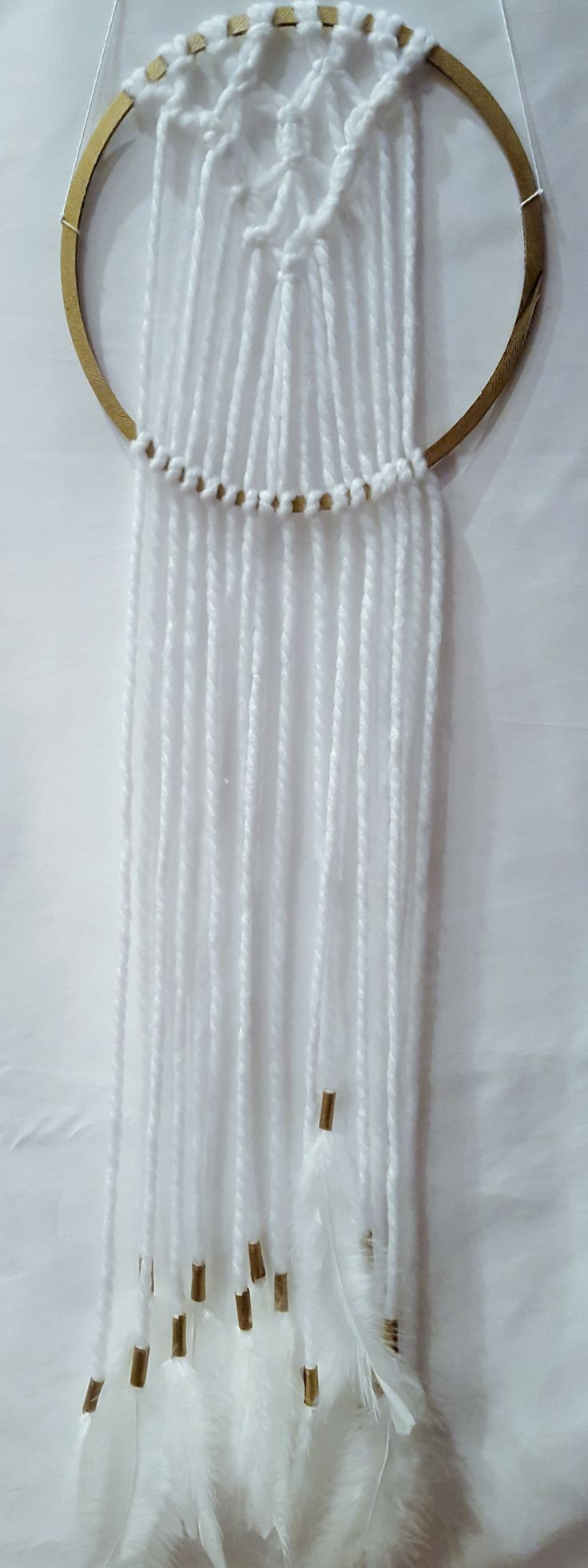 White and gold macrame wall hanging with feathers