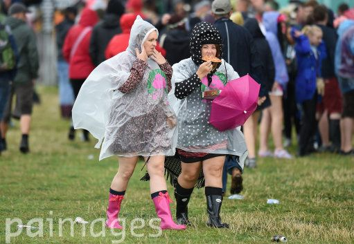 Festival goers enjoy a slice of pizza as they make their way between stages during day two of the V Festival at Weston Park in Staffordshire.