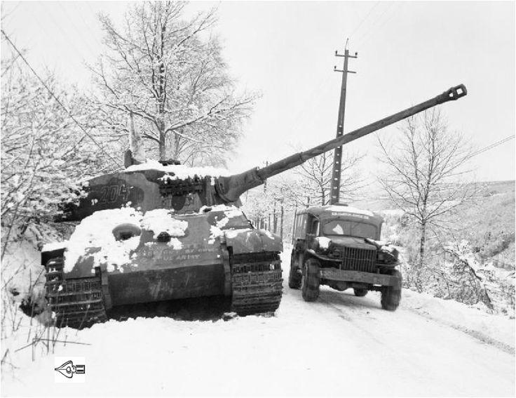 December 1944. Een Amerikaanse ambulancewagen passeert een buiten gevecht gestelde Duitse tank in de regio Bastogne.