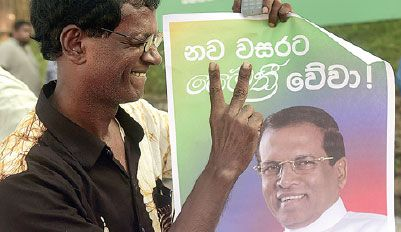 China DailyA supporter of Sri Lanka's main opposition candidate, Maithripala Sirisena, gestures with a poster as people celebrate in Colombo after President Mahinda Rajapaksa conceded defeat in the country's presidential election on Friday. Munir Uz Zaman / Agence France-Presse