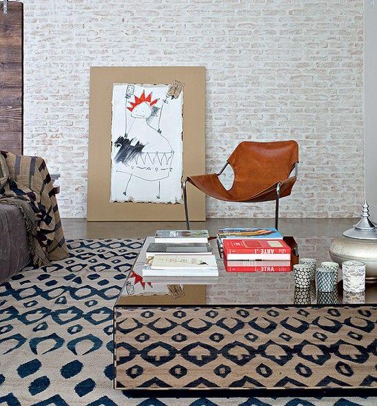 A estampa do tapete da By Kamy é refletida pela mesa de centro, da A Especialista. Cadeira Paulistano, de Paulo Mendes da Rocha, da Dpot, e parede de tijolos cobertos de pintura caiada. Projeto da arquiteta Julliana Camargo