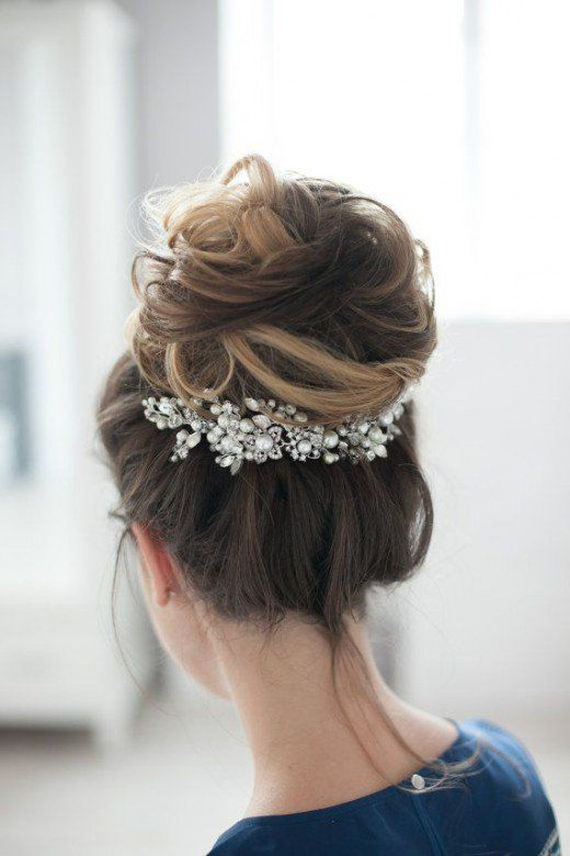 high hair bun which is a little wispy with a gorgeous piece of hair jewellery pinned underneath the bun