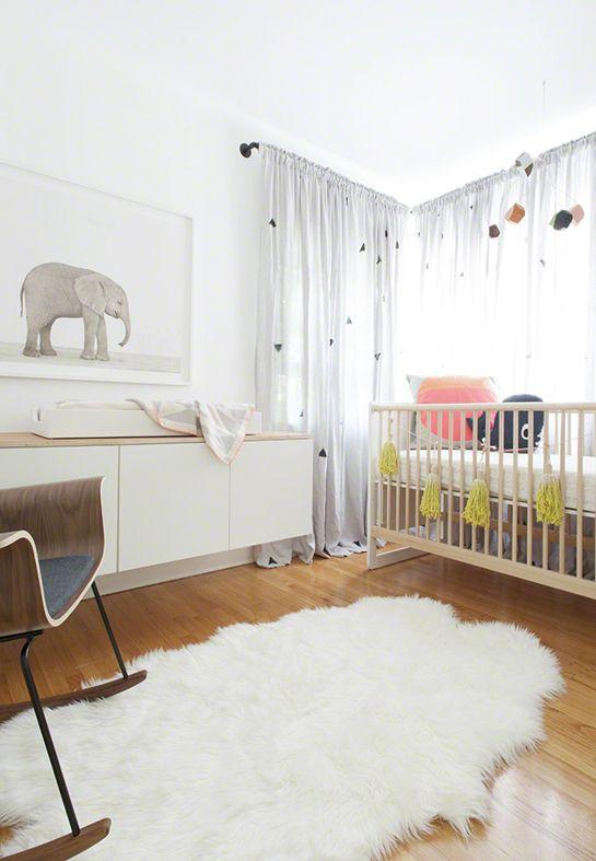 une superbe chambre de bébé : une décoration neutre et minimaliste avec des éléments de décoration tendance ( un tapis en fausse fourrure blanc, une chaise à bascule design, un poster éléphant de Sharon Montrose du site The Animal Print Shop