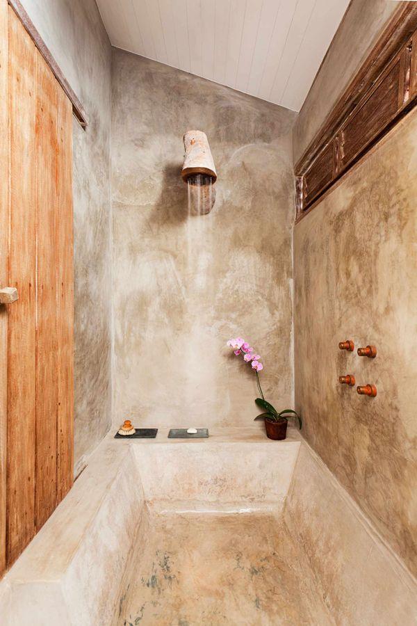 banheira de cimento queimado e chuveiro artesanal de tronco de árvore