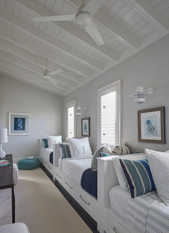 Benjamin Moore Classic Gray. The kids' bedroom feature a row of white built-in beds fitted with storage drawers dressed in white and blue striped bedding and pillows lining a single gray wall illuminated by white nautical wall sconces. A shiplap sloped ceiling accented with white modern ceiling fans hover over a wall of twin built-in beds tucked under windows. Benjamin Moore Classic Gray