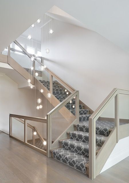For a dramatic statement upon entry, A-List Interiors and Brooklyn lighting design company Shakuff created a cascading light fixture with hand-blown glass spheres that hangs in the open staircase. Connecting the basement to the second level, the staircase is chic and contemporary with a glass railing and large-scale printed runner.