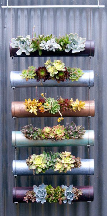Un jardin vertical suspendu à fabriquer, idéal pour un petit balcon / A suspendre le long d'un mur du balcon. Fabrication : tube PVC coupé en sections de 50 cm de long. Avec une scie à métaux, découper une fente de 3 à 4 cm de large et 30 cm de long. Assembler les tubes sur deux cordons d'acier, eux même fixés sur une tringle. Remplir les tubes de terre puis fermer chaque extrémité avec un bouchon PVC. Il ne reste plus qu'à planter de petites plantes grasses pour profiter d'un coin de…