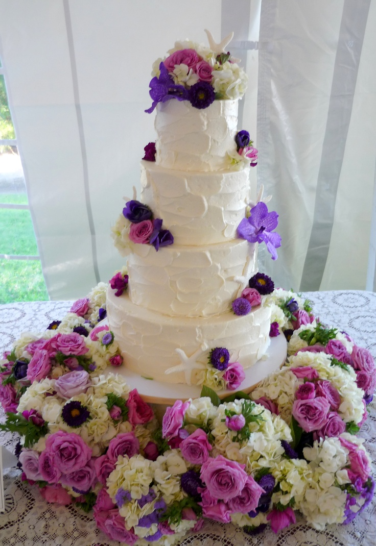 {Swirled Buttercream: Aubergine and Violet Wedding Cake}  We love the wavy nature of swirled buttercream combined with fresh flowers and the maids bouquets!  www.artisanbakeshop.com