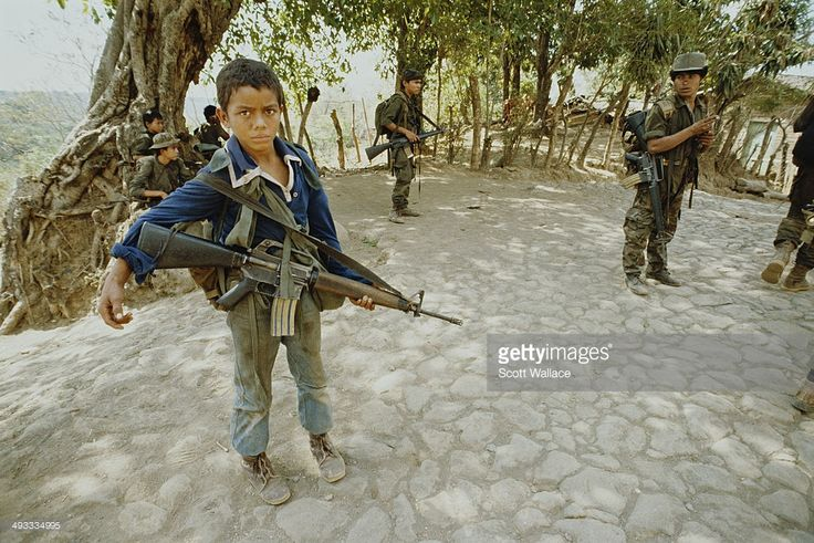 A 12-year-old guerrilla of the FMLN (Frente Farabundo Martí para la Liberación Nacional or Farabundo Martí National Liberation Front) with an M16 rifle in San Francisco Javier, El Salvador, during the Salvadoran Civil War, 1989.