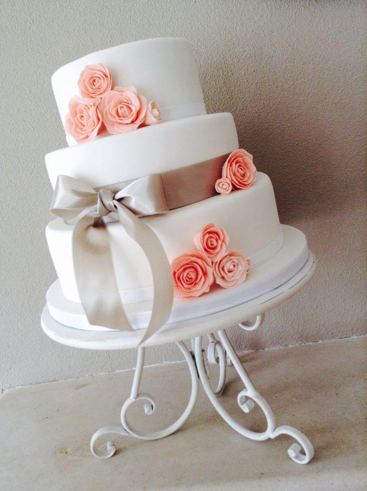 Bruidstaart met grote strik en zalmkleurige roosjes