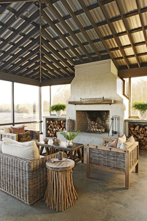 """The screened-in porch boasts a practical galvanized roof, concrete floors, and a cinderblock fireplace covered in a sand wash. Two massive concrete boxes store firewood year-round. """"We find ourselves building fires out here all of the time—even when it's far too warm!"""" Paige says."""