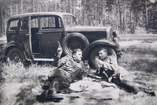 Two Soviet officers resting near road with glasses of alcohol. Circa 1945.