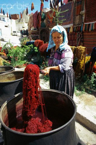 A woman dyes wool for carpet weaving in Goreme, Turkey.