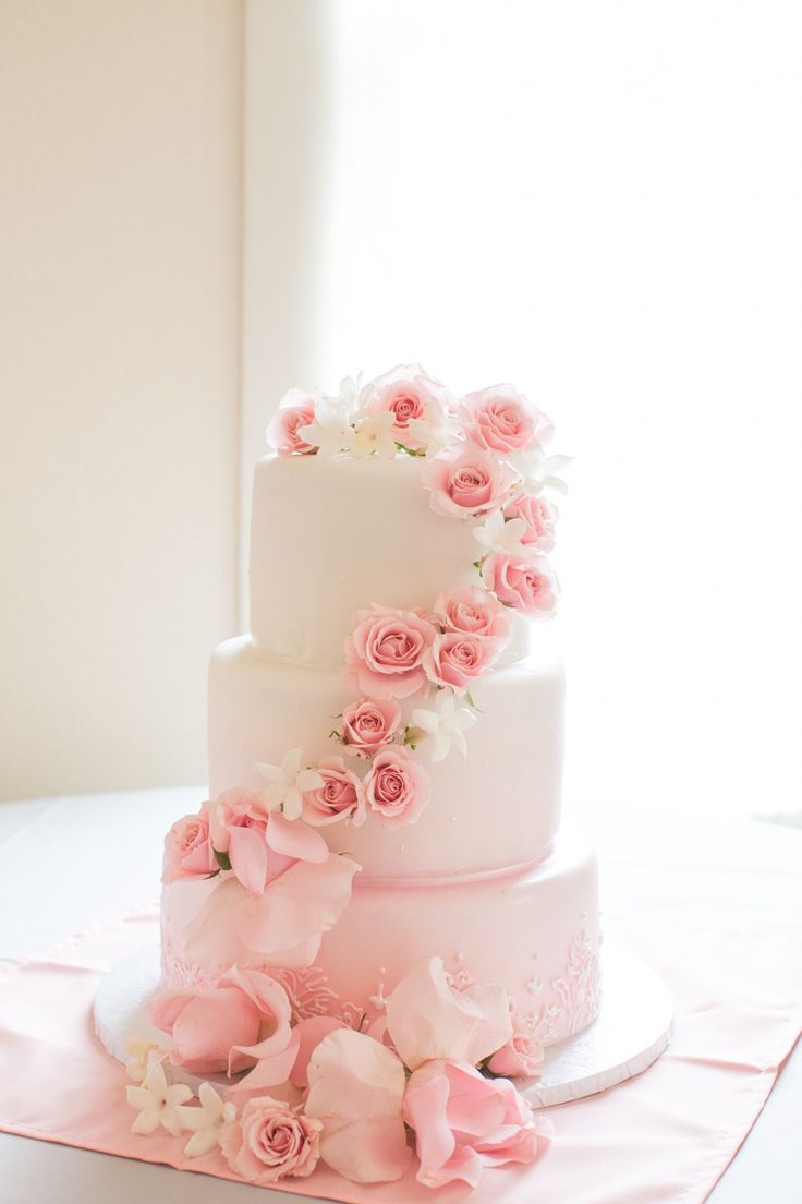 Decorate a classic white cake with cascading flowers in the color that best matches your day. #pink #weddings #weddingcake #pinkweddings
