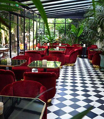 Jardin d'hiver aux fauteuils cosy rouge velours et damiers noir et blanc chic