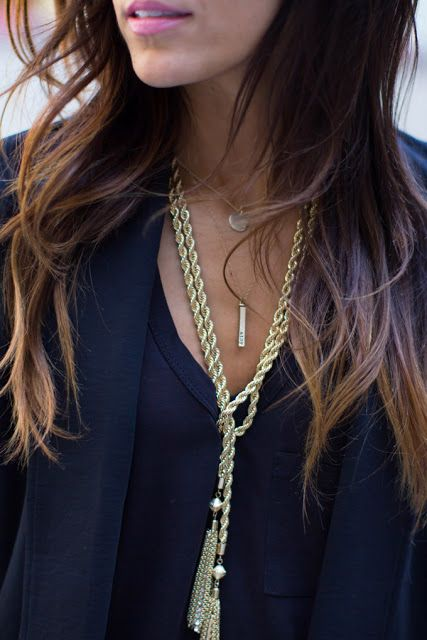 Gold-tone tassel necklace layered with daintier necklaces in gradually shorter lengths