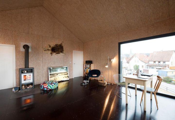 """Una stufa a legno riscalda l'ampio living open space di Unimog House. """"Volevamo creare uno spazio compatto, ma accogliente"""", spiegano gli architetti. L'abitazione si compone di soggiorno, camera da letto e piccolo bagno"""
