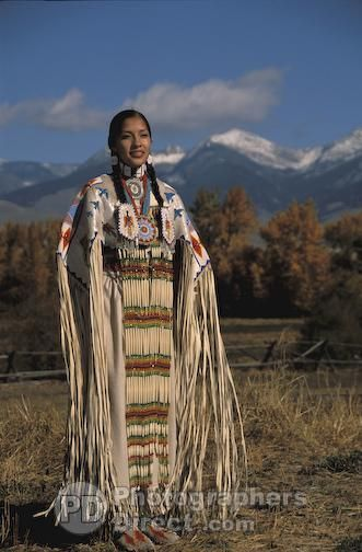 Traditional Lemhi Shoshone woman , Summer Baldwin , dressed in beaded regalia poses with the snowy Sacajawea Peaks in the background during a Ground Blessing ceremony in Salmon Idaho