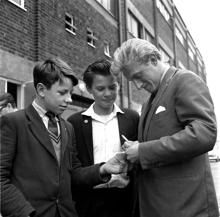 Manchester United's Denis Law signs autographs for fans outside Old Trafford in 1962.