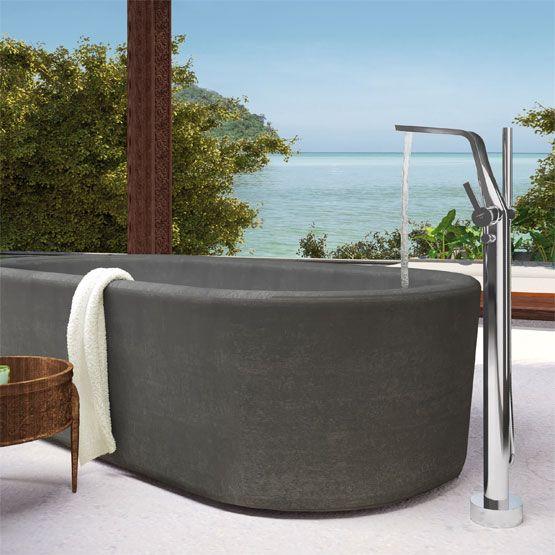 Karibisches Flair, eine freistehende Wanne in dunklem Ton, fließendes Wasser und die Steinberg Wannenarmatur der Serie 270 im Badezimmer