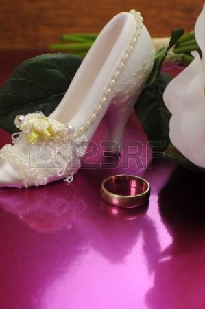 Wedding bridaal bouquet di rose bianche su sfondo rosa con scarpa buona fortuna e fede nuziale. Verticale con copia spazio. photo