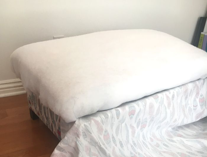 Make your own DIY upholstered storage ottoman starting with lumber from the store - it is super easy! This tutorial covers everything! Wrapping the top in foam and batting