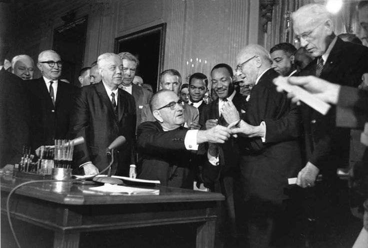 U.S. President Lyndon Johnson passes out some of the 72 pens he used to sign the civil rights bill in Washington D.C. on July 2, 1964.  From left standing are, Rep. Roland Libobati (D-Ill.), Rep. Peter Rodino (D-N.J.), Rev. Martin Luther King Jr., Rep. Emmanuel Celler (D-N.Y.) and Whitney Young, executive director of the National Urban League.  (AP Photo) / Beaumont