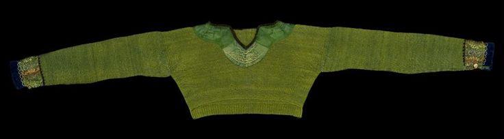 """Mörarp socken i Luggude härad. """"Stickad, grön tröja av ylle. Besatt vid halsen med brunt smalt sammetsband. Bredare grönt sammetsband broderat med gult och grått silke vid handlederna. Blå sammet och polykromt mönstrat sidenband avslutas med liten klippt udd av brunt sammet"""""""