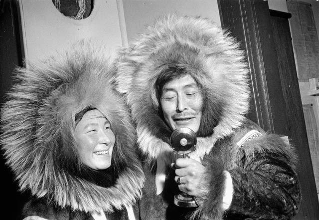 Un couple inuit communiquant avec des amis et de la famille par radio, [1949]. Mention : Richard Harrington / Bibliothèque et Archives Canada / PA-147234