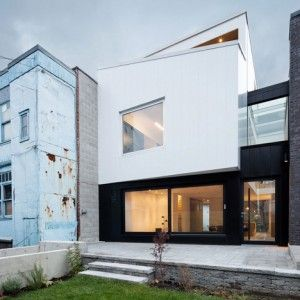 Montreal house by naturehumaine features  a brick front and a monochrome back