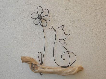 Petit chat et fleur en fil de fer recuit posés sur une branche de bois naturel. Petite perle dans le centre de la fleur. Dimensions : 15*15cm Sur commande. Temps de réalis - 19192462