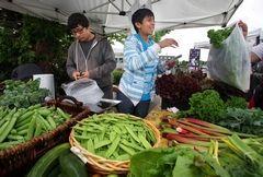 At the Everett Farmers Market, Joseph Rojas and cousin Daniel Mendez bag vegetables harvested from their grandparents' farm.