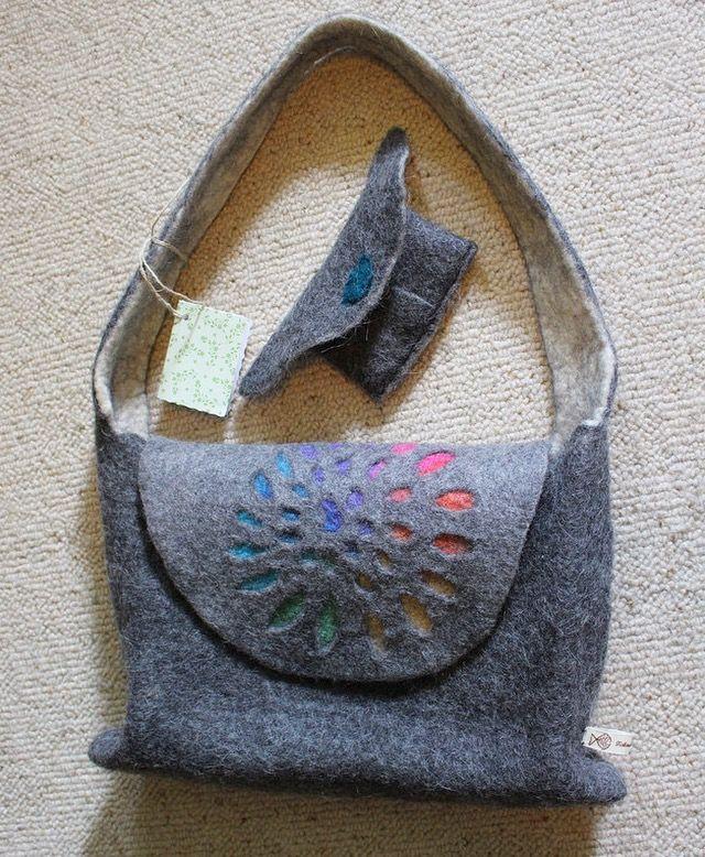 Diese ungewöhnliche Tasche ist komplett in einem Stück gefilzt und auch der Schulterriemen ist in diese wunderschöne Filztasche eingearbeitet und nicht eingenäht. Sie kann mit einem Druckknopf geschlossen werden .  An der gesamten Tasche ist keine einzige Naht.