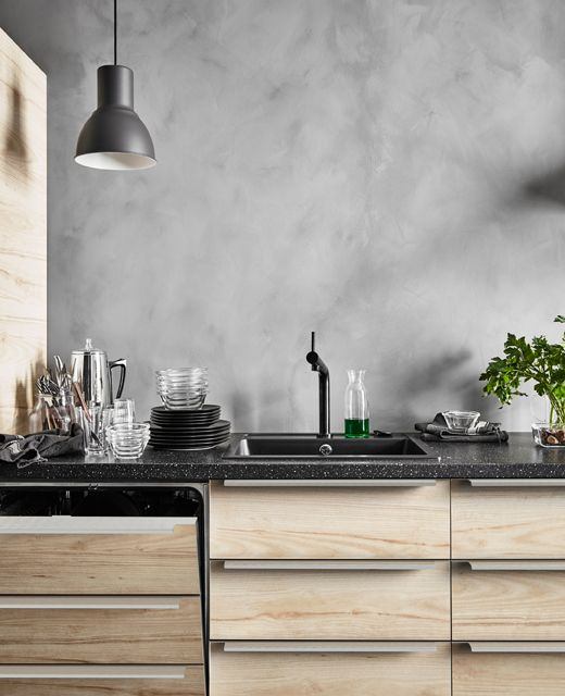 A dishwasher with integrated ash effect panels in a row of base cabinets in a modern rustic kitchen with gray, concrete-looking walls