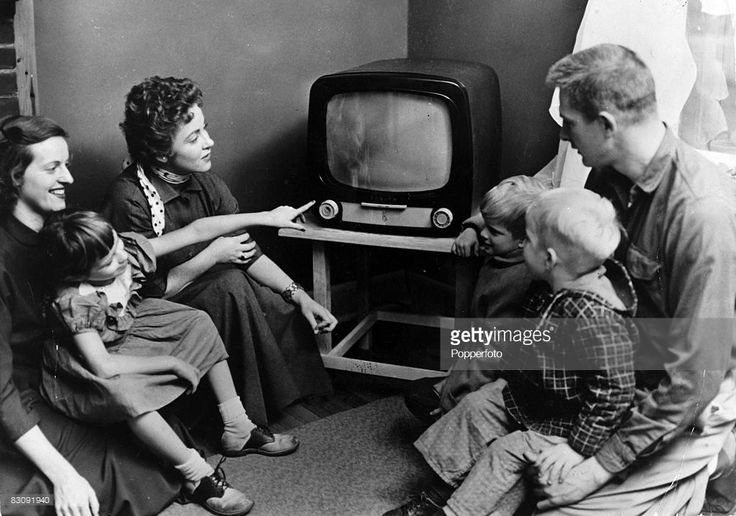 Foto stock : People Entertainment. Domestic appliances. U.S.A. pic: circa 1954. A family gather around the television in an American home.