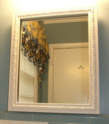 When you remodel on a budget, you have to get creative. So....instead of buying a new medicine cabinet, here's quick and easy way to cover the old one. Simply get an old frame, spray paint it white, and clip it to the front of the existing medicine cabinet mirror.