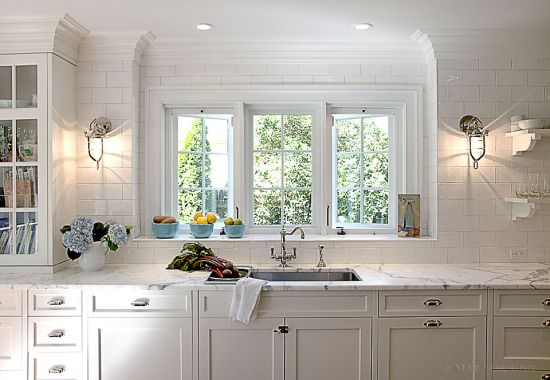 sconces on either side of the kitchen window are a nice touch and help to illuminate the space since there are no upper cabinets