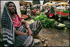 Comoros... A Comoron woman sits at the edge of a street market in Moroni, the capital of this steep volcanic island nation beset by environmental and political instability.