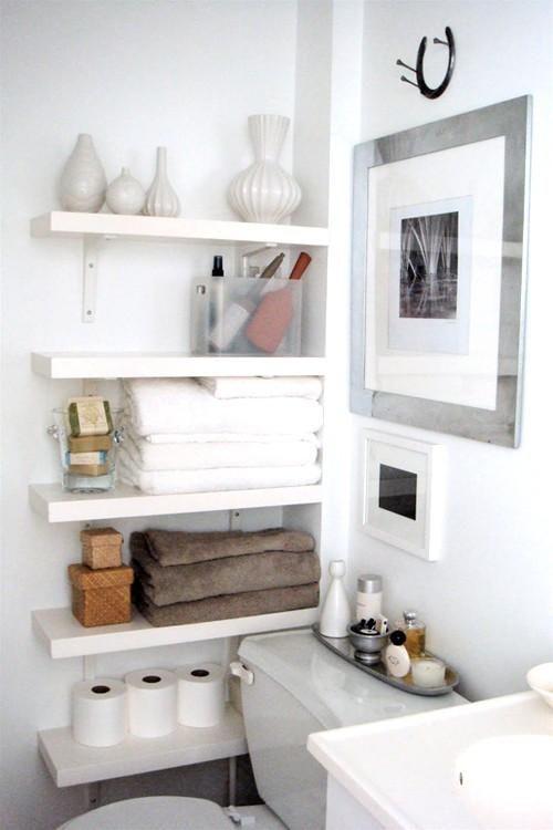 白い壁に白い棚、ストックのトイレットペーパーやタオルなどもごちゃごちゃしない色使いが綺麗。上の棚の花瓶のフォルムの違いや、馬蹄の壁飾りなども洒落ている。