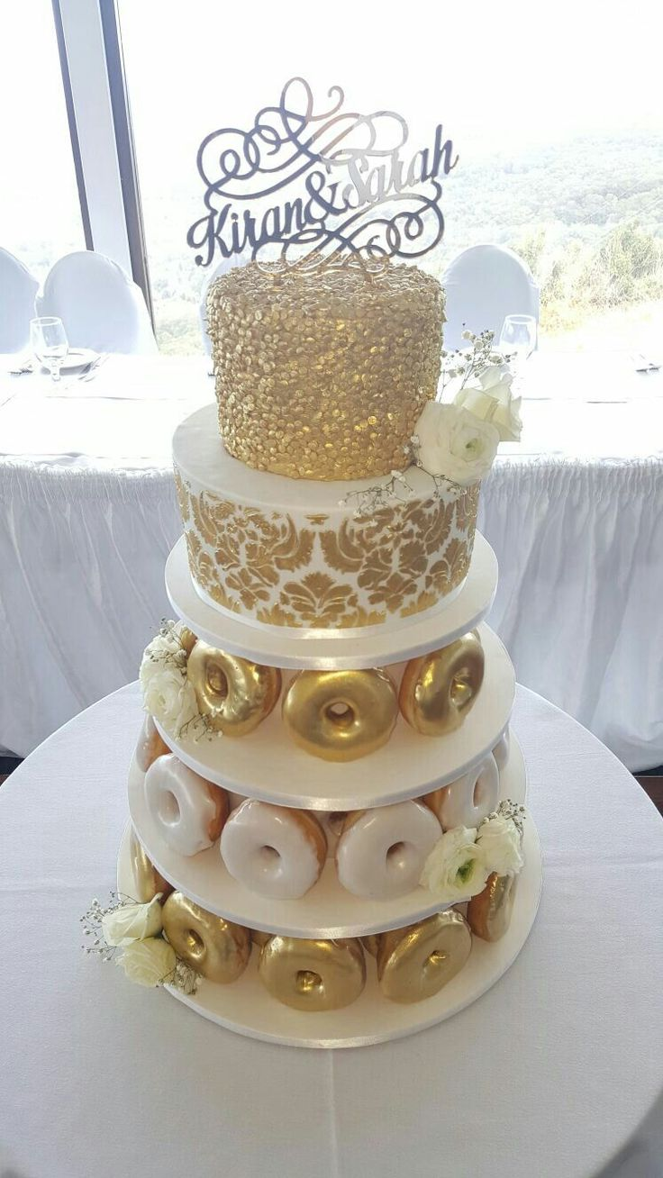 My wedding cake! Krispy Kremes donut cake with gold damask and gold sequins. The…