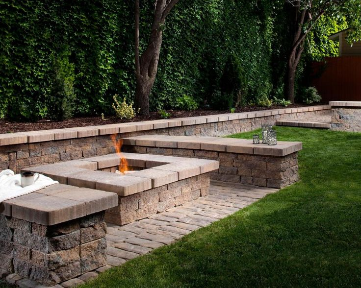 A square fire pit fits in with the linear design of the wall and seating area. The space is softened with the trees and greenery. It's made with pavers and blocks manufactured by Amcor Masonry Products.