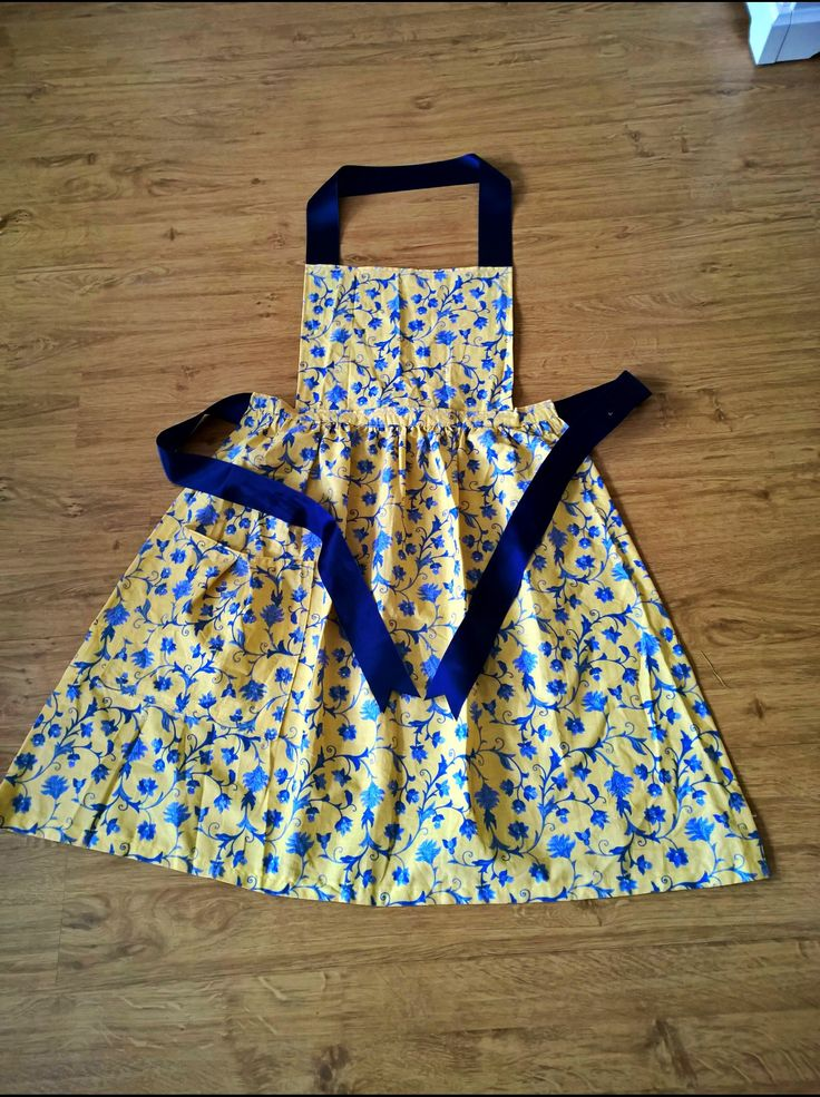 Today's project was this vintage inspired apron. It's made from an old skirt. The skirt was a simple design made up of two pieces and a gathered waistline, so I simply opened up the sideseams and cut the waistband so I had half a skirt. I then prettied up the edges and used the other half of the skirt to make the top and the pleated pocket (it's barely visible in this pic). Finally I added some blue ribbon and ta-daaa!